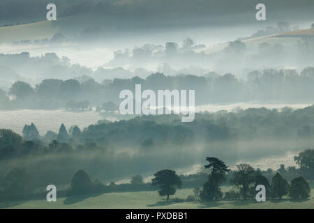 Morning mist hangs in valleys of the the South Downs National Park on an autumn morning, near Bishops Waltham, Hampshire, UK Saturday October 20, 2018 - Stock Photo