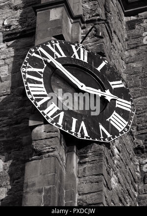 Vintage roman numerals clock on an old stonw wall in black & white. - Stock Photo