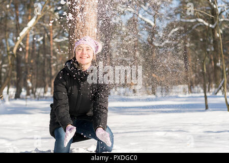 Girl throws snow up. Portrait of the beautiful girl throwing snow in the winter. Happy young woman plays with a snow in sunny winter day. - Stock Photo