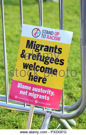 Stand Up To Racism. A Migrants & Refugees Welcome Here Placard at Manchester Piccadilly Gardens Manchester UK Afternoon - Stock Photo