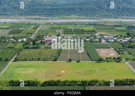 Paraglider landing on field, circle and heart shape on green grass field,countryside aerial view, at Luye Township, Taitung County, Taiwan - Stock Photo