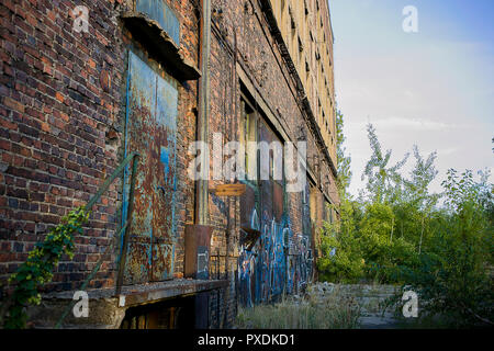 Old train factory ruins with industrial brickwork and big blue doors on a warm sunny day are bringing nostalgic feelings - Stock Photo