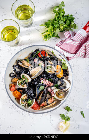 Homemade seafood Black pasta spaghetti with clams mussels octopus vongole in pan with white wine on marbled background - Stock Photo