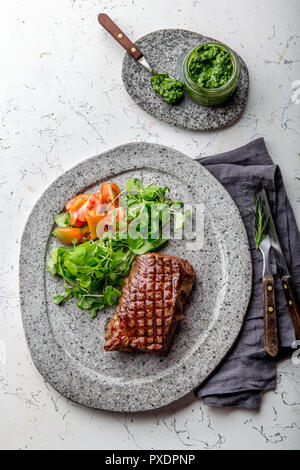 Grilled beef steak tenderloin on gray stone plate with salad and chimichurri sauce - Stock Photo