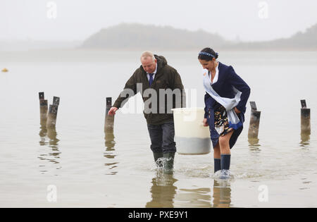 22 October 2018, Mecklenburg-Western Pomerania, Goldberg: Till Backhaus (SPD), Agriculture Minister of Mecklenburg-Western Pomerania, and Jeannette Dehmel, 1st Fisher Queen of Mecklenburg-Western Pomerania, are releasing pre-stretched (fed) young eels in Lake Goldberg. For 25 years, the 'Landesanglerverband MV' has occupied eels worth around 100,000 euros annually. The campaign 'Save the European Eel' should contribute to the conservation of eels in Mecklenburg-Vorpommern. Photo: Danny Gohlke/dpa-Zentralbild/dpa - Stock Photo