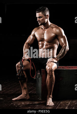 Male sitting after using resistance bands after training exercise - Stock Photo