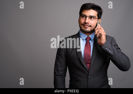 Young handsome bearded Persian businessman wearing eyeglasses - Stock Photo