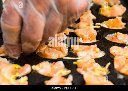 Close up baking prawns in baking pan with holes - Stock Photo