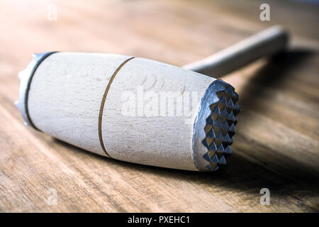 A Wooden Meat Mallet Lying Down On A Table - Stock Photo
