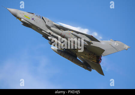RAF Royal Air Force Panavia Tornado GR4 jet fighter bomber plane climbing at speed with vapour condensation forming above the wing. Blue sky - Stock Photo