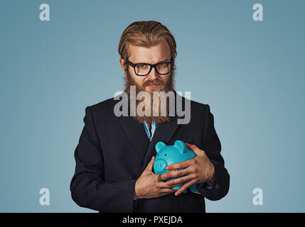 Young greedy stingy Bearded hipster businessman man holding piggy bank Isolated on blue studio wall Background. Negative face expression human emotion - Stock Photo