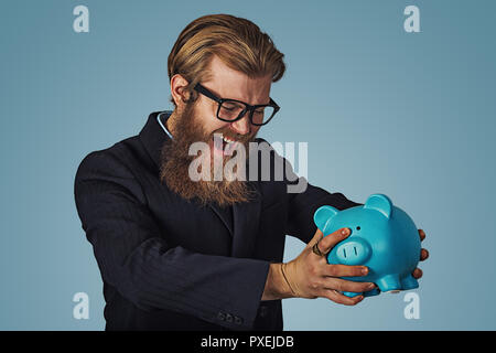 Unhappy man in glasses angry at his piggy bank trying to broke it up, Bearded hipster businessman Isolated on blue Background. Negative face expressio - Stock Photo