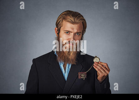 Time is ticking. Bearded hipster serious business man holding showing pocket watch Isolated on gray grey studio wall Background. Negative face express - Stock Photo