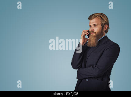 Bearded hipster business man holding talking by mobile phone isolated on blue studio wall Background. Serious face expression, human emotion, body lan - Stock Photo