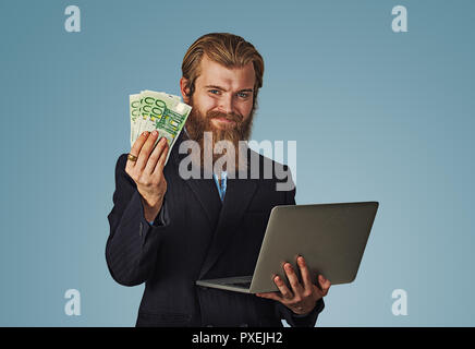 Successful smiling young man holding laptop building online business making money euro bills cash. Beginner IT entrepreneur success economy concept Be - Stock Photo