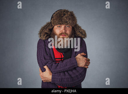 Having cold I am going to get sick. Worried hipster serious guy man embracing himself trying to warm up in fur hat sweater and scarf looking at you ca - Stock Photo