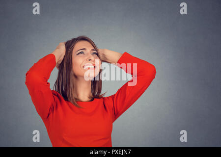 angry woman covering ears looking up stop loud noise - Stock Photo