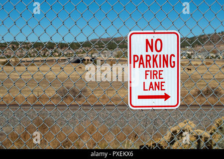 No parking fire lane sign on fence in parking lot - Stock Photo