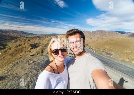 Active happy couple taking selfie on travel in high Atlas mountains, Ouarzazate, Morocco. - Stock Photo