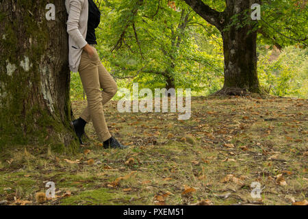 Crop view of young adult woman with autumn casual outfit in the park/woods - Stock Photo
