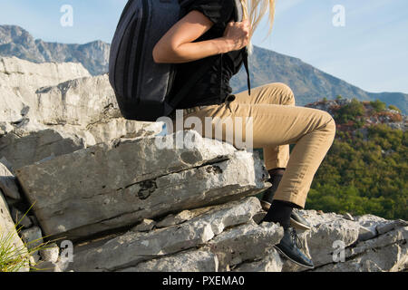 Young woman with backpack sitting on the edge of the mountain cliff against beautiful mountains peak. Travel and lifestyle concept - Stock Photo