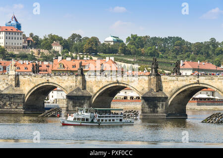 PRAGUE, CZECH REPUBLIC - SPETEMBER 2018: Tourist sightseeing river cruise boat passes under the famous Charles Bridge on the River Vltava in Prague. - Stock Photo
