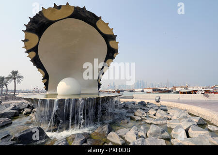 Doha / Qatar – October 10, 2018: The Pearl Monument on the Doha corniche, with traditional dhows and the skyscrapers of the West Bay area in the dista - Stock Photo