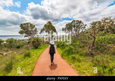 A woman on a walking trail at Wireless Hill Park with a view over the Swan River. Booragoon, Perth, Western Australia - Stock Photo