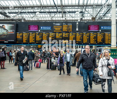 Passengers in the concourse in front of a departures board in Edinburgh Waverley Railway Station, Scotland, UK - Stock Photo