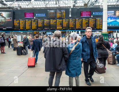 Passengers waiting and arriving in front of the Departures board at Waverley Railway Station, Edinburgh, Scotland, UK - Stock Photo