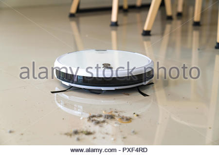 Robotic vacuum cleaner on carpet in cozy living room - Stock Photo