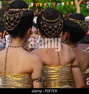A group of Thai students backstage, shortly  before performing classical Thai dances, in Santichaiprakarn Park, Bangkok, Thailand - Stock Photo