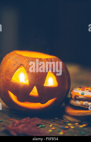 Halloween background with pumpkin on the wooden table. Smile pumpkin head with candles, fall leaves and Halloween cookies. Close up - Stock Photo