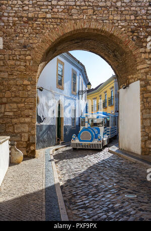 Faro, Algarve,  Portugal- April 29, 2018: Tourist tram passing through the narrow  winding street of the historical center of Faro - Stock Photo