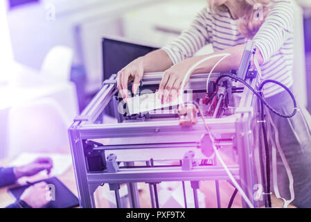 Two business workers standing near 3D printer while printing important presentation - Stock Photo