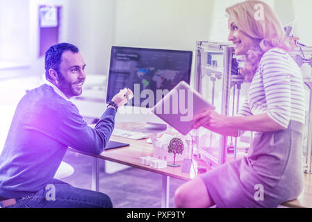 Dark-haired bearded office worker helping his colleague using 3D printer - Stock Photo