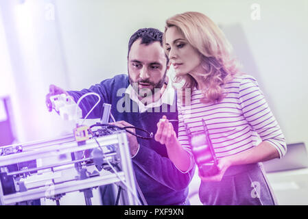 Bearded dark-haired man showing his colleague the way of using laser printer - Stock Photo