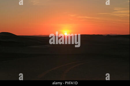 Stunning sunset over the sand dune of Huacachina desert with people and dune buggy in distance, Ica region, Peru - Stock Photo