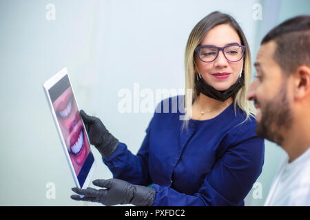 female dentist shows electronic device to male patient for smile design - Stock Photo