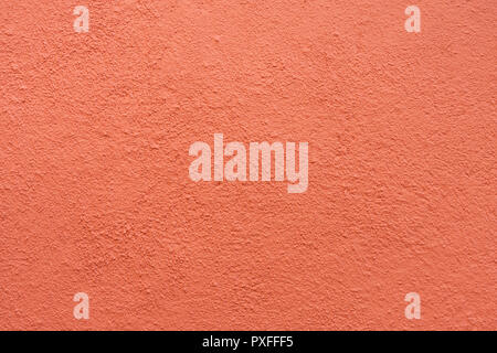 Stucco wall - Maroon red stucco textured wall background with natural light. - Stock Photo