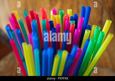 A collection of new plastic, disposable colored straws standing upright in a cup. - Stock Photo