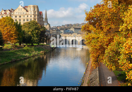 The famous landmarks of Pulteney Weir and Pulteney Bridge surrounded by vibrant autumnal trees on the River Avon in Bath, UK. - Stock Photo