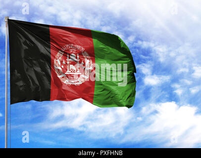 National flag of Afghanistan on a flagpole in front of blue sky. - Stock Photo