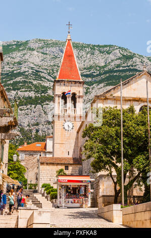 Makarska, Сroatia - June 23, 2014: Cozy and vibrant medieval Old Town street of Makarska. Tourists and local people walking by the streets. - Stock Photo