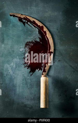 closeup of an old and rusty sickle full of blood, placed on a dark green rustic surface - Stock Photo