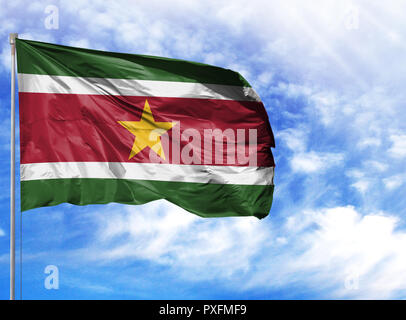 National flag of Suriname on a flagpole in front of blue sky. - Stock Photo