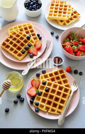 Belgian waffles with strawberries and honey on gray background. Healthy breakfast concept - Stock Photo