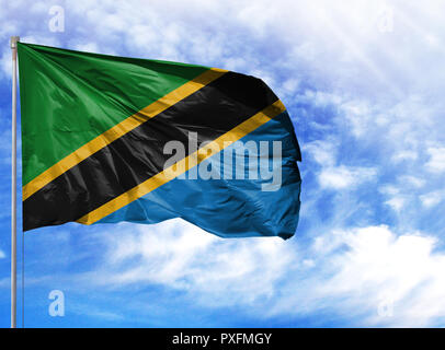 National flag of Tanzania on a flagpole in front of blue sky. - Stock Photo