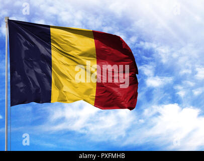 National flag of Chad on a flagpole in front of blue sky. - Stock Photo