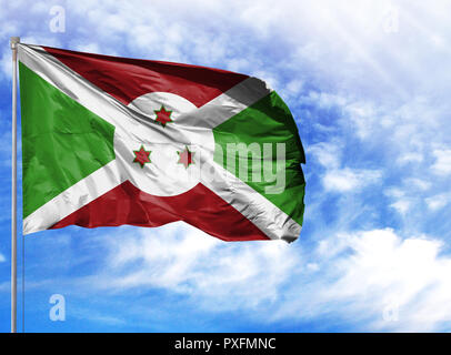 National flag of Burundi on a flagpole in front of blue sky. - Stock Photo